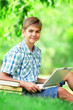 Teen boy with books and laptop in the park.