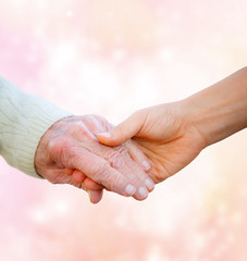 Senior Lady Holding Hands with Young Woman