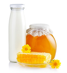 Sweet honey in glass jars with flowers, honeycombs and bottle of