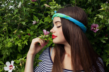 trendy teenager model with big lips smelling flowers