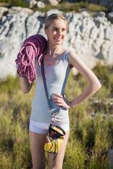Smiling woman holding climbing equipment