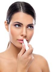 Woman applying balsam on lips