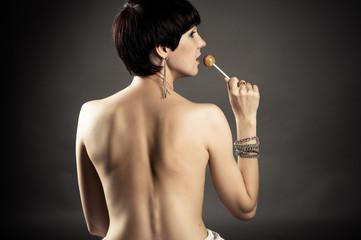 beautiful naked woman holding a lollipop