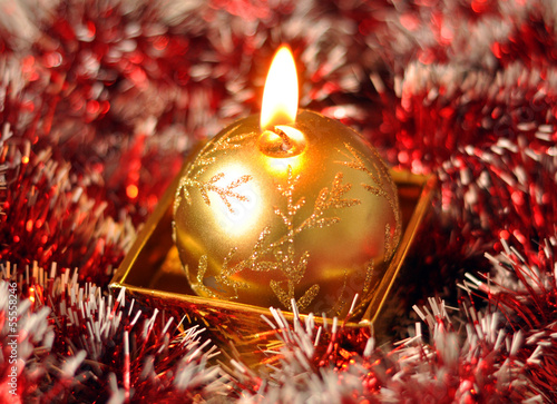 Golden Christmas candle on the red background