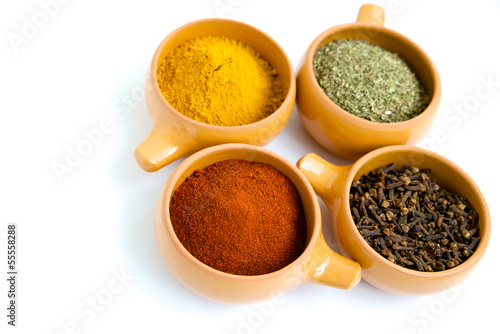 Four cups with spices on a white background