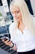 junge blonde frau mit einem mobiltelefon smartphone