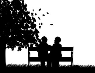 Elderly couple sitting on bench in park in autumn or fall