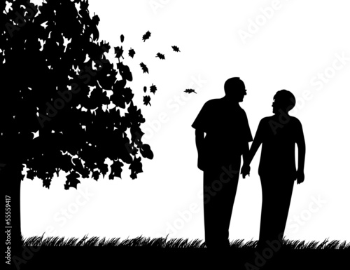 Elderly couple walking in park in autumn or fall