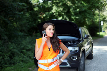 junge Frau mit Warnweste telefoniert