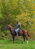 Cowgirl relaxing with horse in autumn woods