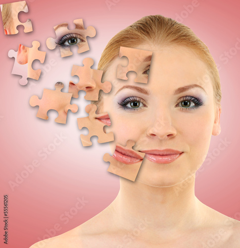 Beautiful girl with parts of skin on puzzles on pink background