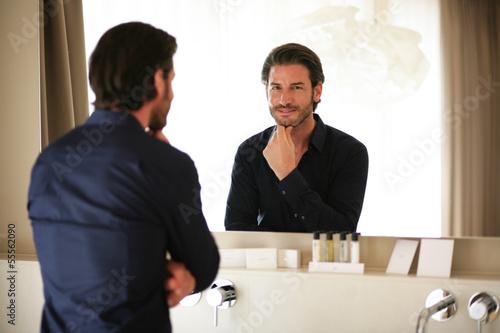 Mann betrachtet sich im Spiegel
