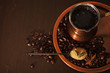 Coffee in copper coffee pot with teaspoon of sugar and spices