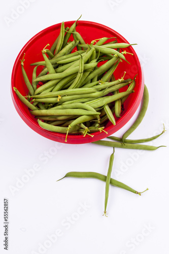 Green beans in red bowl - white background