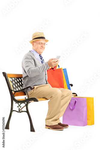Senior man seated on a bench with shopping bags and typing a sms