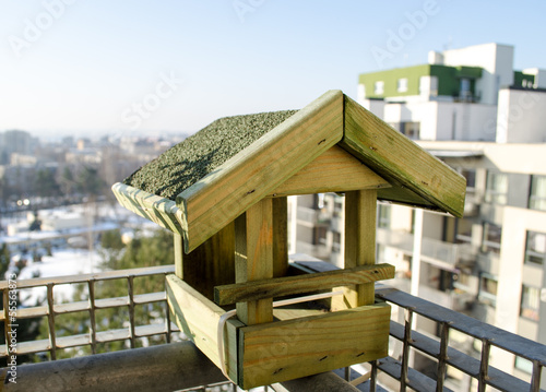 wooden small bird feeder on the balcony edge