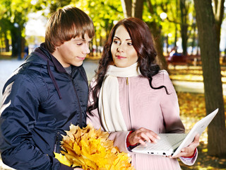 Couple holding white laptop outdoor.