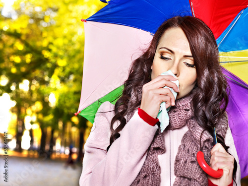Woman sneezing handkerchief outdoor.