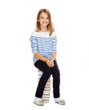 little student girl sitting on stack of books