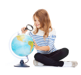 child looking at globe with magnifier