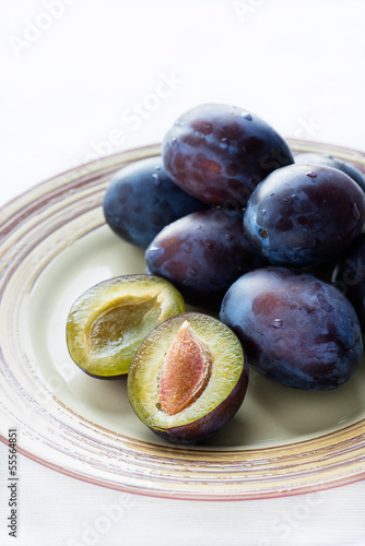Fresh plums on plate  over light background