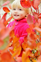 toddler girl standing in bushes