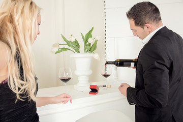 Man pouring red wine with a open ring box