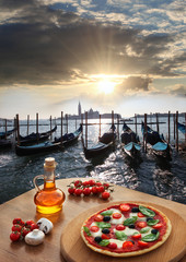 Classic Italian pizza in Venice against gondolas, Italy