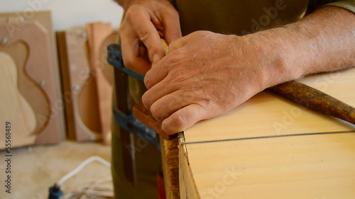 Luthier with a chisel manufacturing a guitar