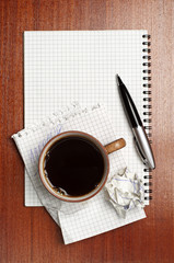 Cup of coffee, notebook and pen