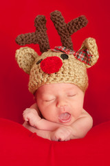 Newborn Baby Wearing a Red-Nosed Reindeer Hat