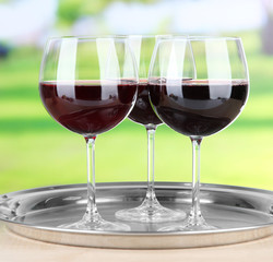 Wine glasses on  tray, on bright background