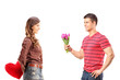 Female holding red heart behind and man giving flowers to her