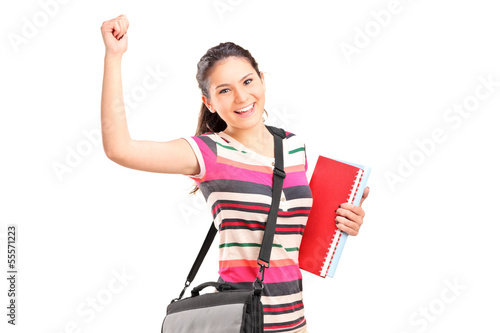 Happy female student holding notebooks