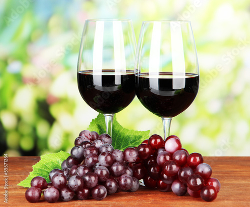 Ripe grapes and glasses of wine, on bright background