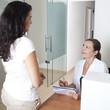Rezeptionistin macht Termin mit Patientin aus