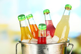 Bottles with tasty drinks in bucket with ice cubes, in bright