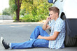 Man calling repair service after car breakdown