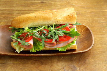 baguette sandwich with arugula, ham and tomatoes