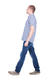 Back view of going  handsome man in jeans and a shirt.