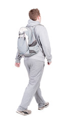 back view of walking  man  with backpack.