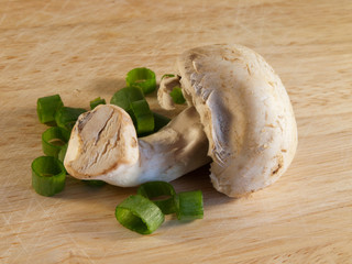 Champignon on wooden board with green onion