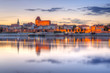 Torun old town reflected in Vistula river at sunset, Poland