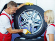 Car mechanic explains tyre changing to a trainee