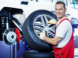 Fototapety Motor mechanic changes a tyre with new alu rim