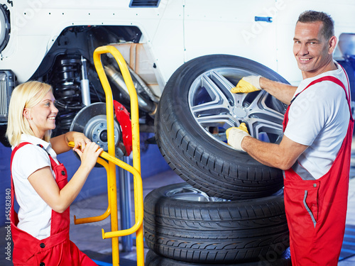Auto mechanics change car tyres in a garage