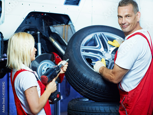 Mechanic and apprentice change car tyres in a garage