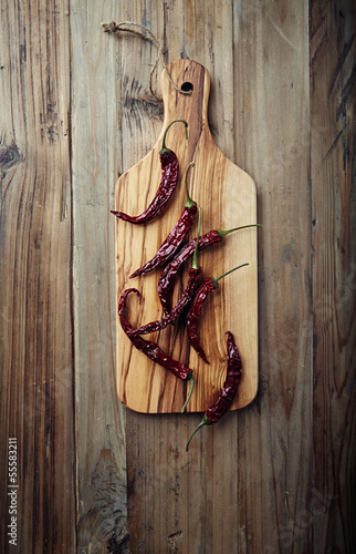 Dried chili peppers on wooden kitchen board