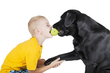 A child and a dog bite an Apple