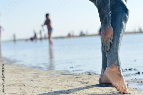 Woman applying mineral blue mud on legs at Sivash lake